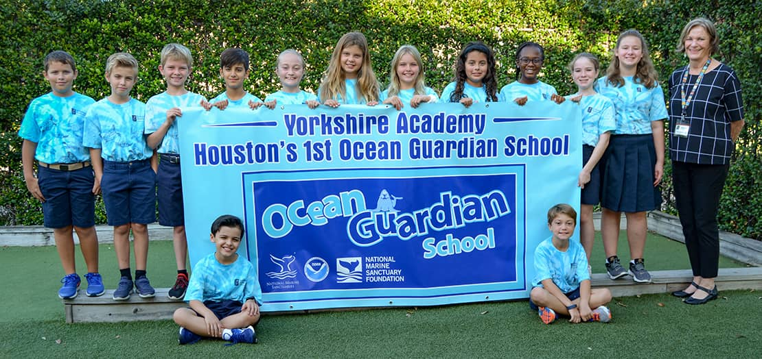 Students holding a large Houston 1st Ocean Guardian School banner